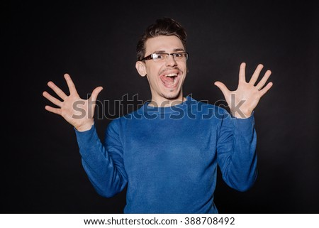 young man making numbers sign gesture with hand fingers. emotions, facial expressions, feelings, body language, signs. image on a black studio background.