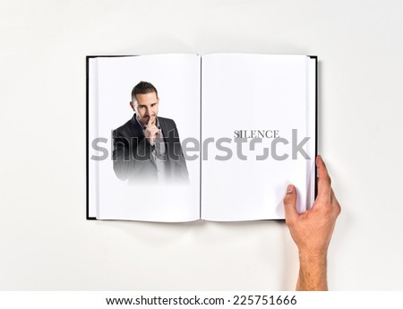 Young man making silence gesture printed on book - stock photo