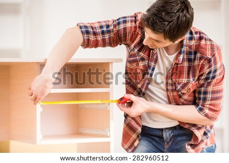 Young man measuring home furniture with measure tape  Repair concept. Furniture Repair Stock Images  Royalty Free Images   Vectors
