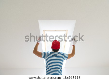 Young man measuring the wall of new home with tape measure - stock photo