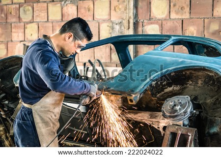 Young man mechanical worker repairing an old vintage car body in messy garage - Safety at work with protection wear - stock photo