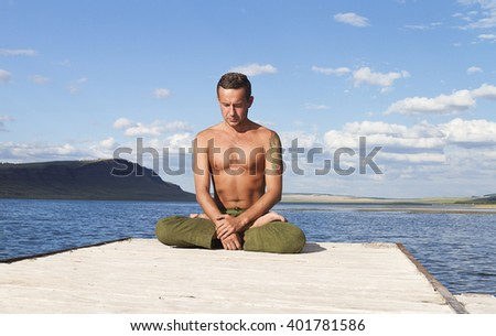 young man meditating in a lotus position on the lake. yoga practice. breathing exercises.