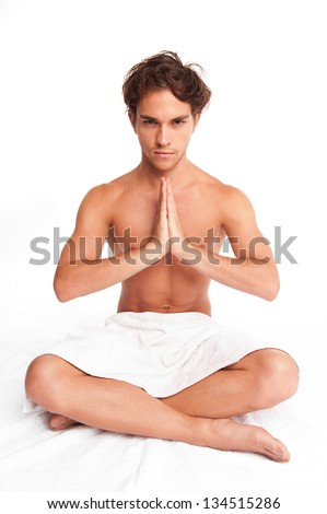 young man meditating in a peaceful enviroment. hands together facing each other and looking at camera. studio shot. - stock photo