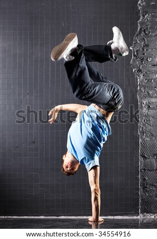 Young man modern dance. On dark wall background.
