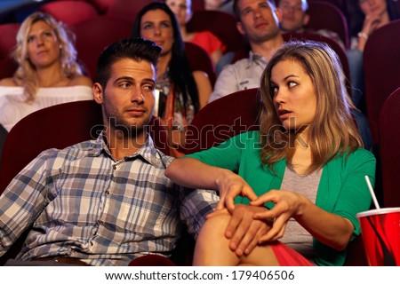 Young man molesting pretty girl in cinema, touching leg. - stock photo