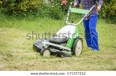 Young man mowing the lawn with a lawnmower machine - stock photo