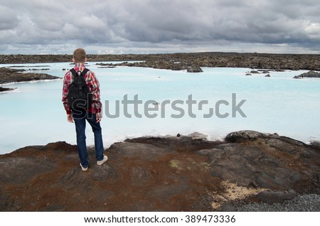 Young man observing blue lagoon waters in the lava field under the cloudy sky of Iceland.