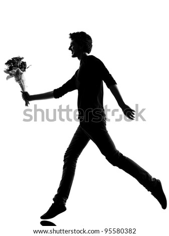 young man offering flowers bouquet silhouette in studio isolated on white background - stock photo