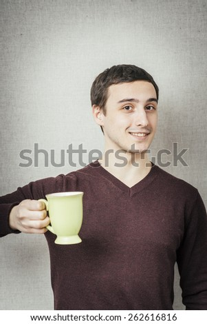 young man offers a cup of tea - stock photo