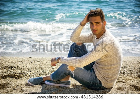 Young Man on a Beach in a Sunny Summer Day - stock photo