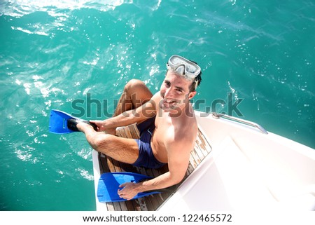 Young man on a boat steps putting flippers on - stock photo