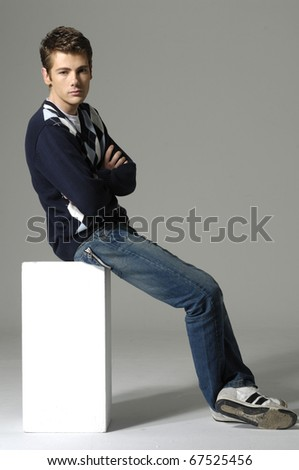 young man on a cube on gray background - stock photo