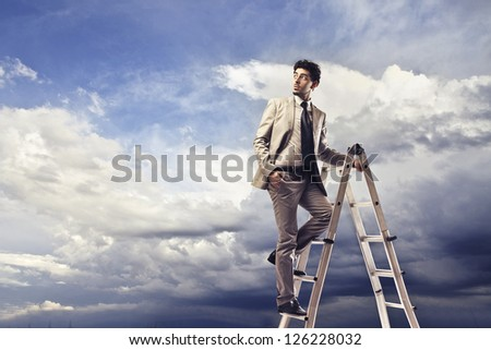 Young man on a scale with a blue cloudy sky in the background - stock photo