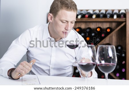 young man on a wine tasting session on the olfactory phase with the wineglass in the nose is writing down in a wine tasting sheet at a restaurant - focus on the man face