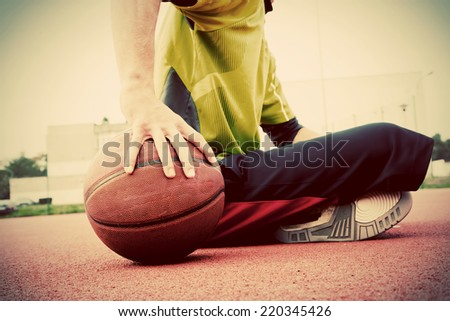 Young man on basketball court. Sitting and dribbling with ball. Streetball, training, activity. Real and authentic, vintage mood. - stock photo