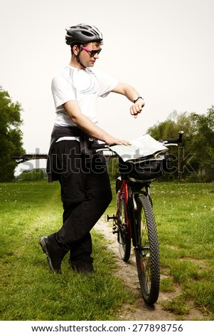 Young man on bicycle enjoying spring day with sport - stock photo