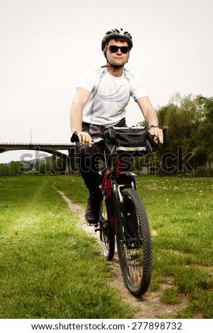 Young man on bicycle enjoying trip near river  - stock photo