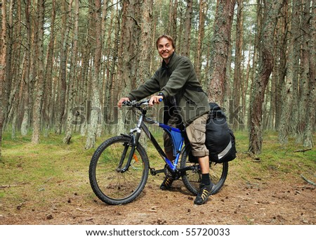Young man on bicycle with backpack in forest - bicycle travel