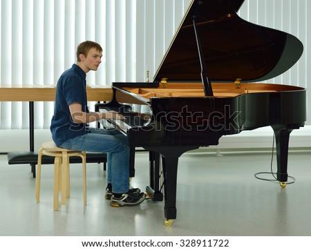Young man on black piano rehearses - stock photo