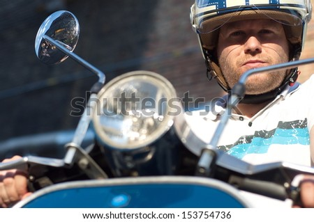 Young man on blue scooter - stock photo
