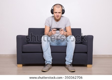 young man on couch playing games or watching movie on mobile phone - stock photo
