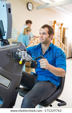 Young man on exercise bike with physical therapist assisting patient in hospital - stock photo