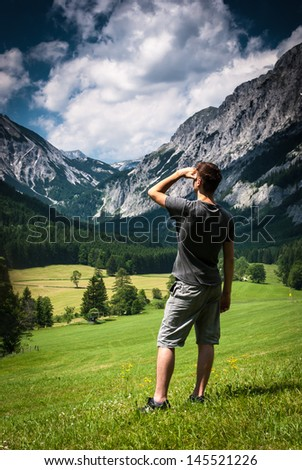 Young man on field in mountains looking forward.