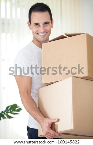 Young man on moving day holding and carrying cardboard box - stock photo