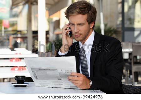 Young man on phone while reading newspaper - stock photo