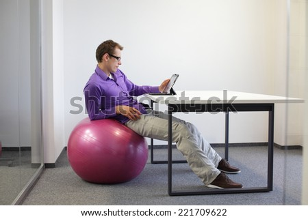 young man on stability ball working with tablet in office  - relaxed position at workstation -   - stock photo