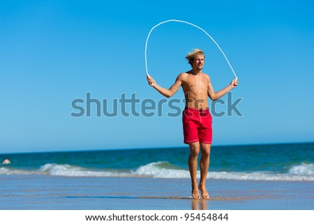 Young man on the beach is jumping rope  in his vacation