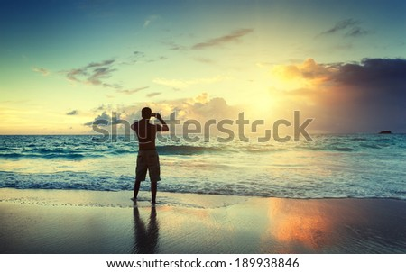 young man on the beach take photo on mobile phone - stock photo
