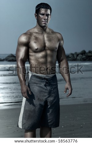 young man on the beach with swim trunks - stock photo