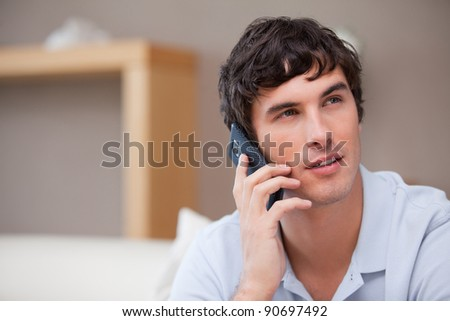 Young man on the cellphone sitting in the living room - stock photo