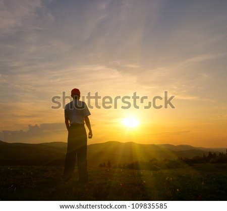 young man on the green lawn in the mountains at sunset