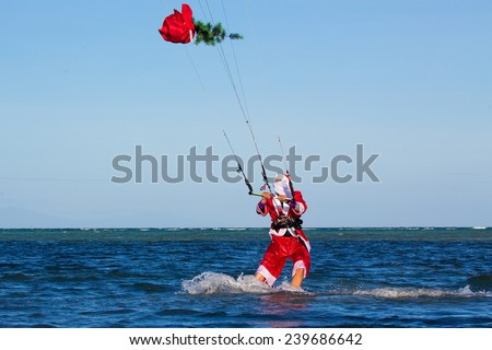 Young man on the kite in the costume of Santa Claus with a Christmas tree in the bag . Christmas and New year on a tropical island. Extreme Sport Kitesurfing - stock photo