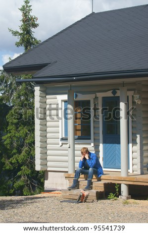 Young man on the porch of a cottage in the woods