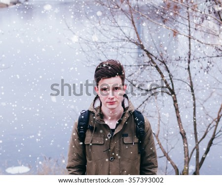 Young man on the river and first snow - stock photo