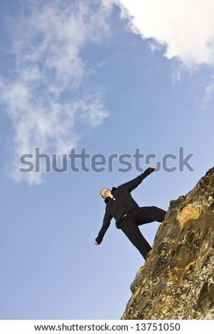 Young man on the rocks in defiant gesture - stock photo