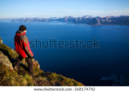 Young man on the top of mountain Festvagtinden with picturesque scenery of chain of Lofoten islands, Norway - stock photo