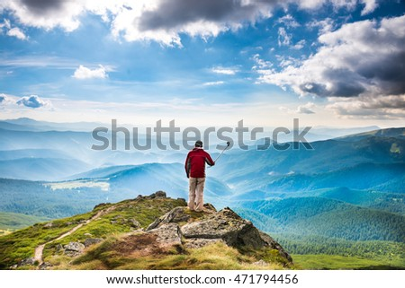 Young man on the top of mountain taking picture with camera on selfie stick