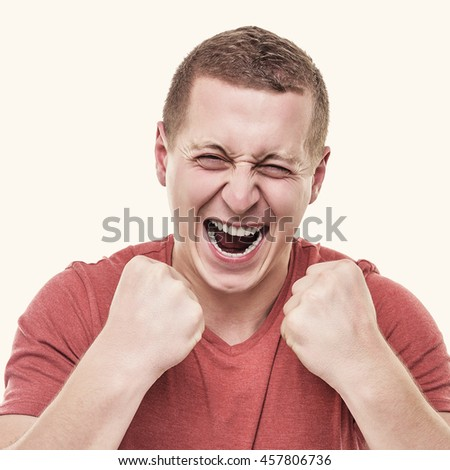 Young man on white background, rejoices victory. Toned photo. - stock photo