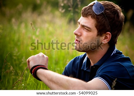 young man outdoor portrait in grass