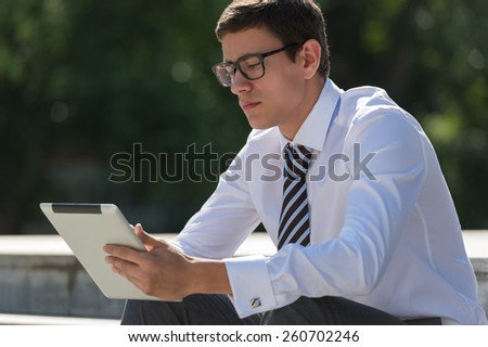 Young man outdoors at park using tablet computer - stock photo