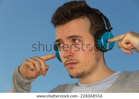 Young man outdoors with headphones or earphones sound and blue sky background  - stock photo