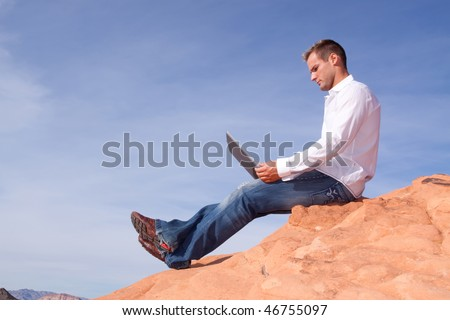 Young man outdoors with his laptop - stock photo
