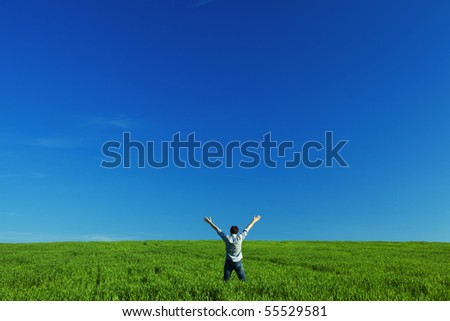 young man outstretched arms in green field against the blue sky - stock photo
