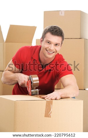 Young man packing boxes to move in new flat. smiling male with roll of brown packaging - stock photo