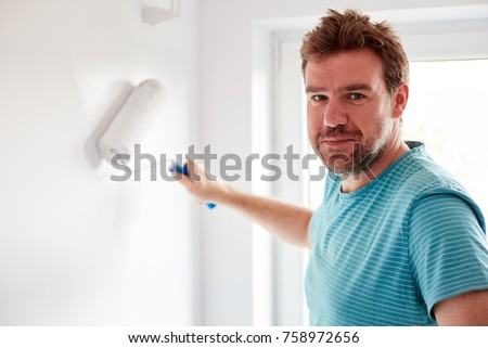 Young man painting a wall on white in a modern home