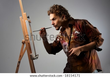 young man painting on a canvas - stock photo